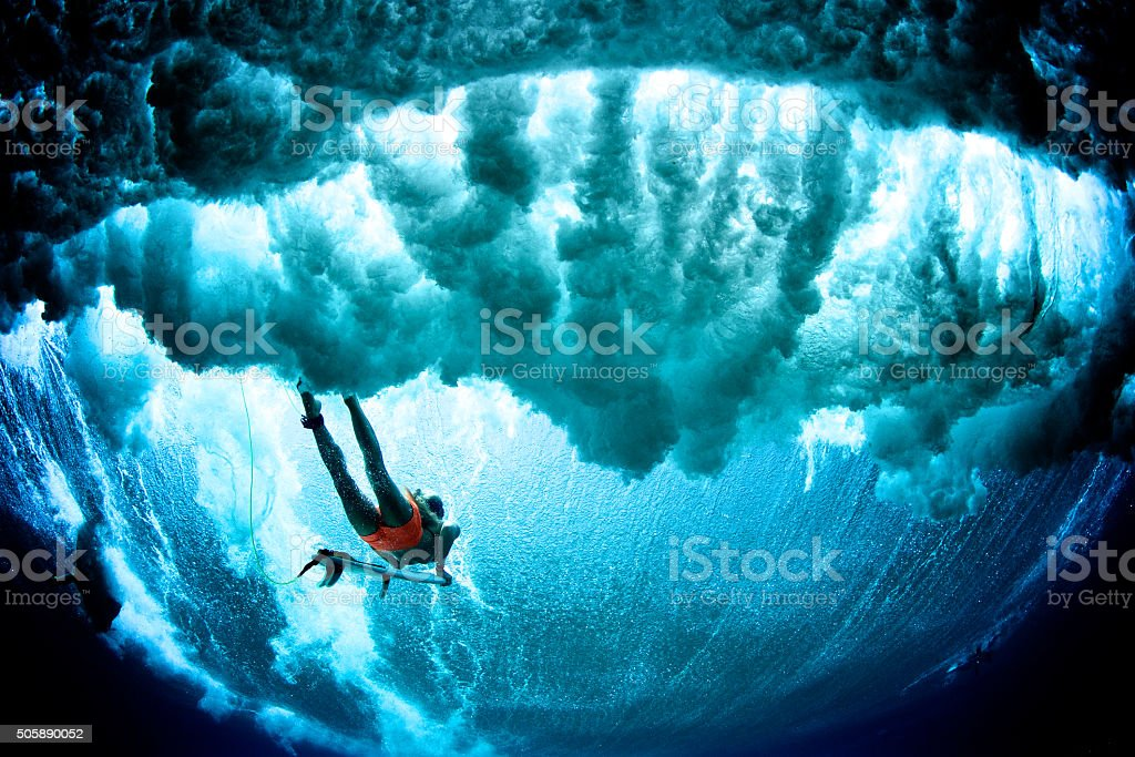 Dark cloudy duck dive surfer stock photo