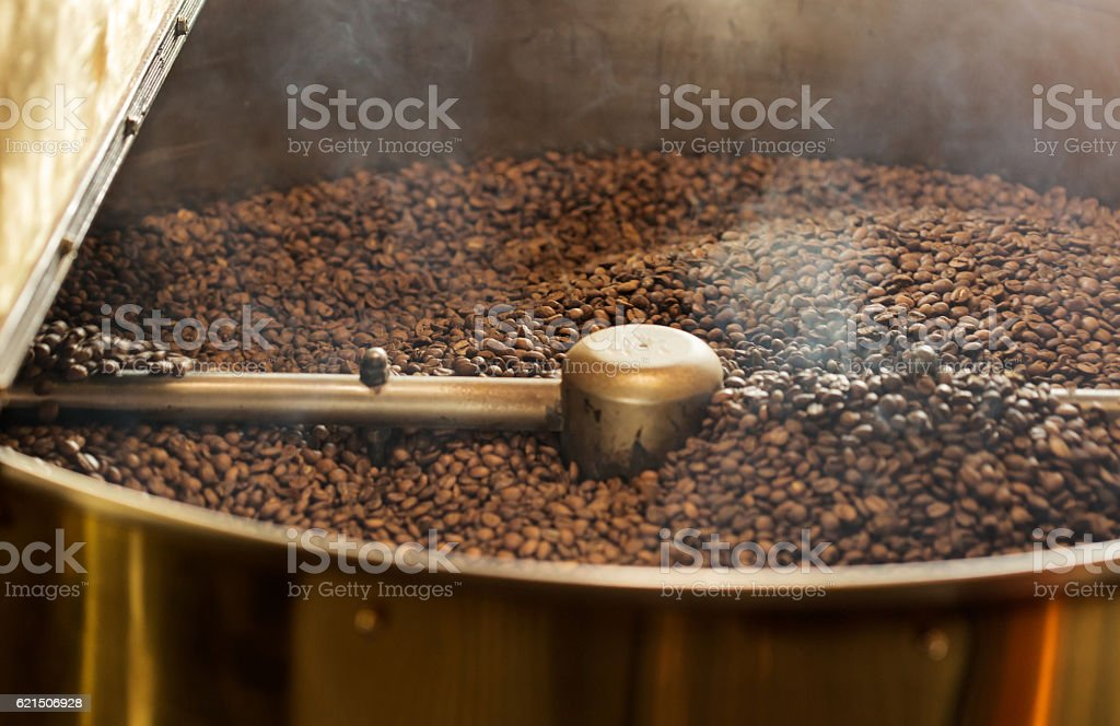 Dark coffee beans in professional roasting machine stock photo
