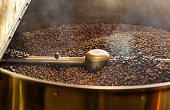 Dark coffee beans in professional roasting machine