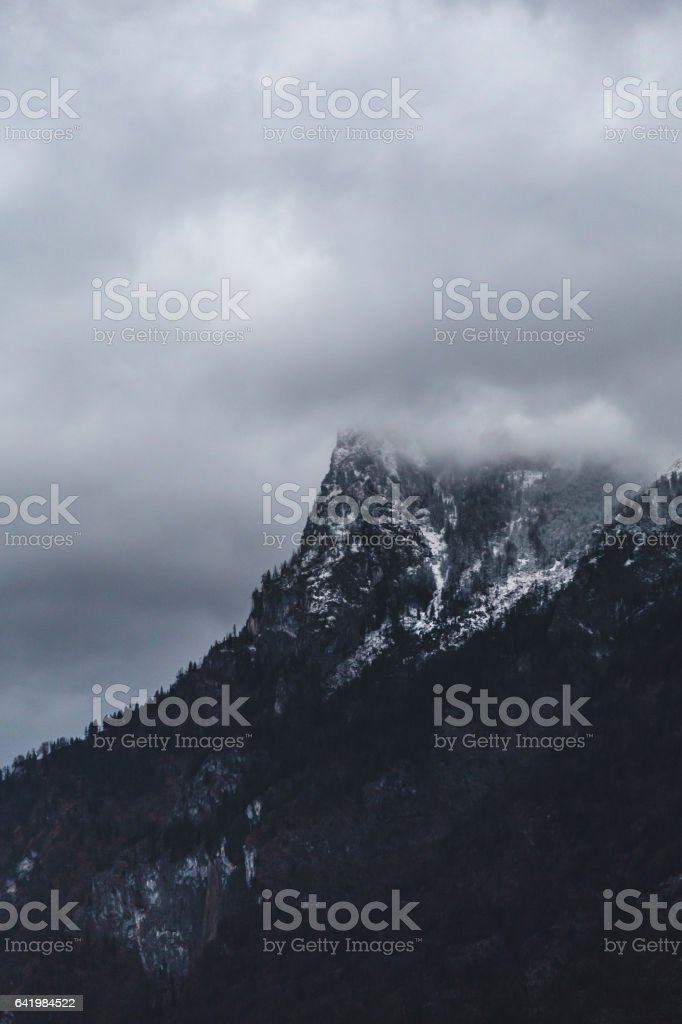 Dark cold mountain peak covered with snow touching clouds stock photo