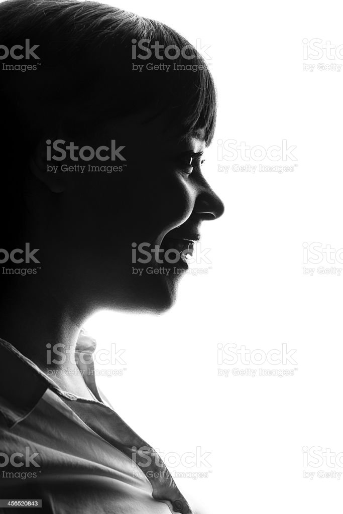Dark colored profile of smiling woman stock photo
