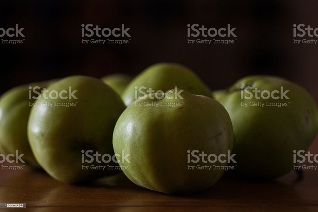 Dark Contrasty Cooking Apples on a Wooden Table stock photo