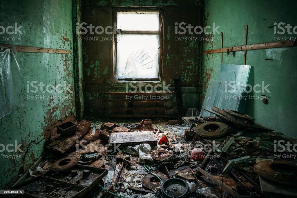 Dark dirty room with garbage in an abandoned industrial building,...