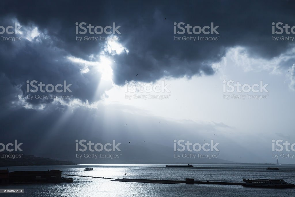 Dark dramatic sky with sunlight rays over sea stock photo
