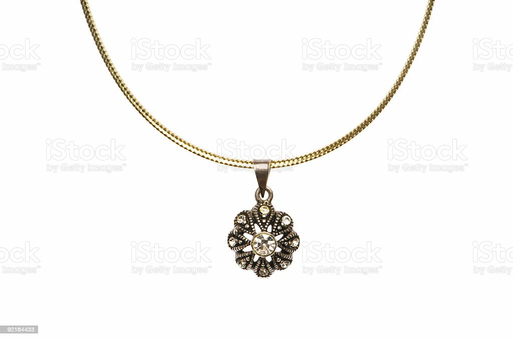 A dark floral jewel pendant hanging from a gold chain royalty-free stock photo