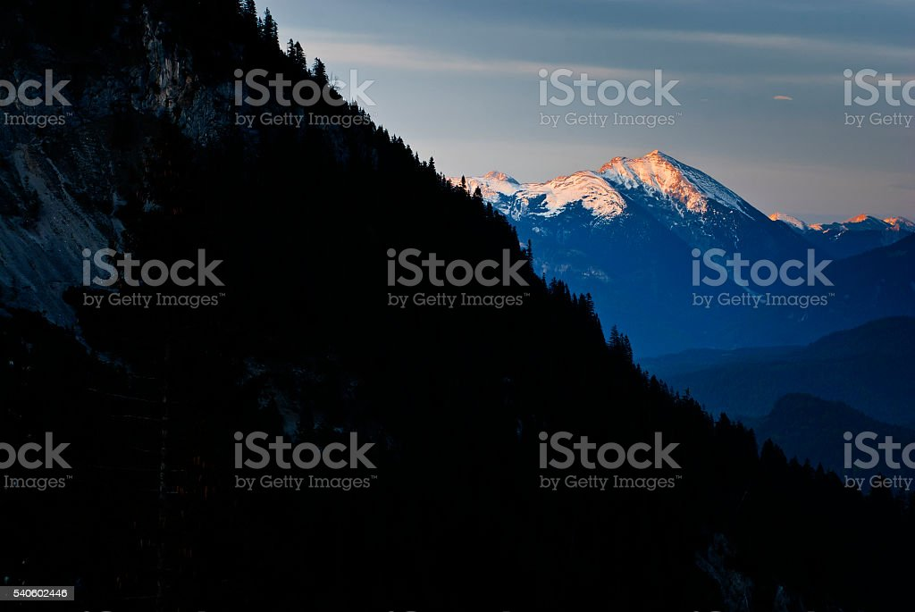 Dark forest and Karwendel mountains in evening light stock photo