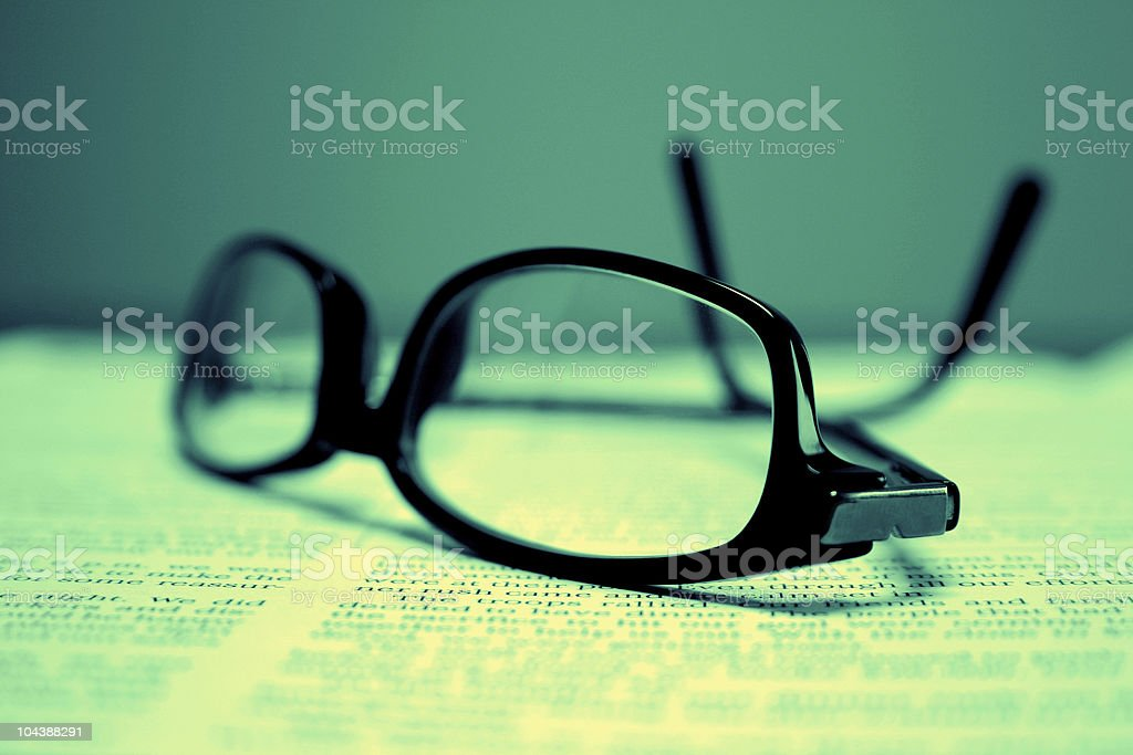 Dark glasses over a text with a bluish green background royalty-free stock photo