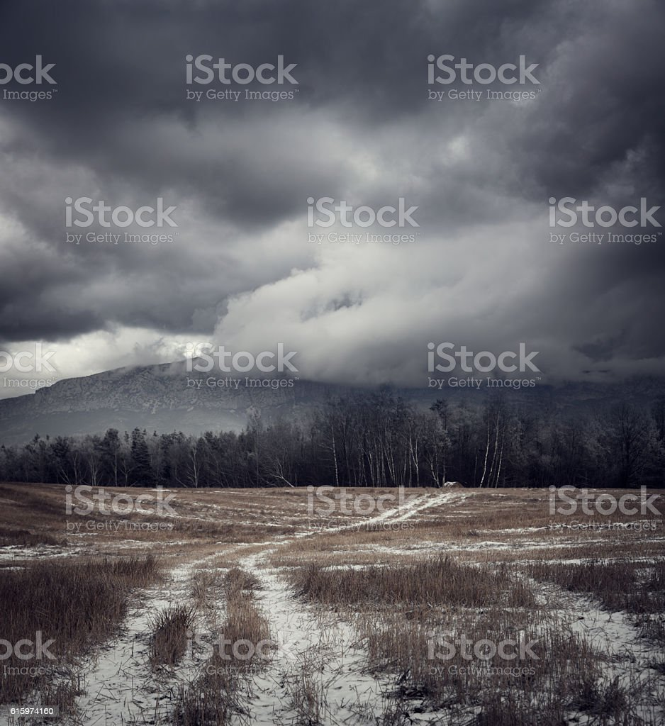Dark Gloomy Landscape with Country Road in Snow stock photo