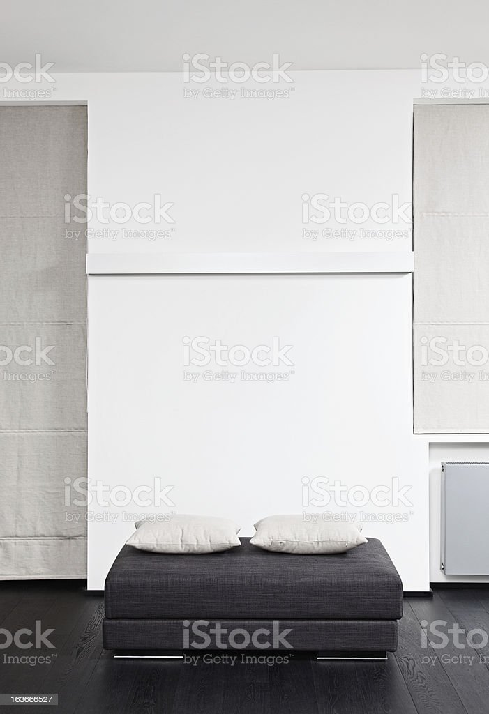 Dark gray padded stool with white pillow stock photo
