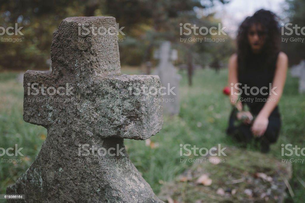 Dark hair girl kneeling next to stone grave stock photo