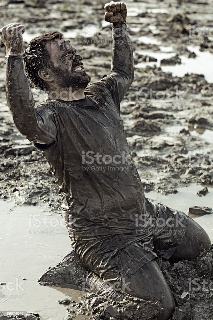 Dark haired man celebrating during a mud run stock photo