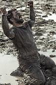 Dark haired man celebrating during a mud run