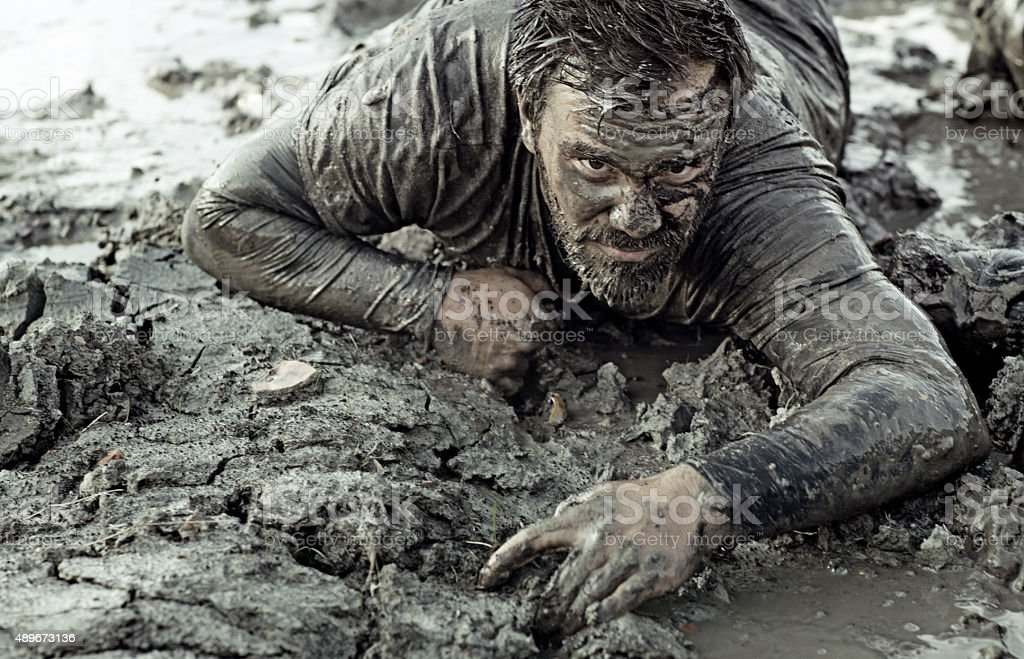 Dark haired man crawling during a mud run stock photo