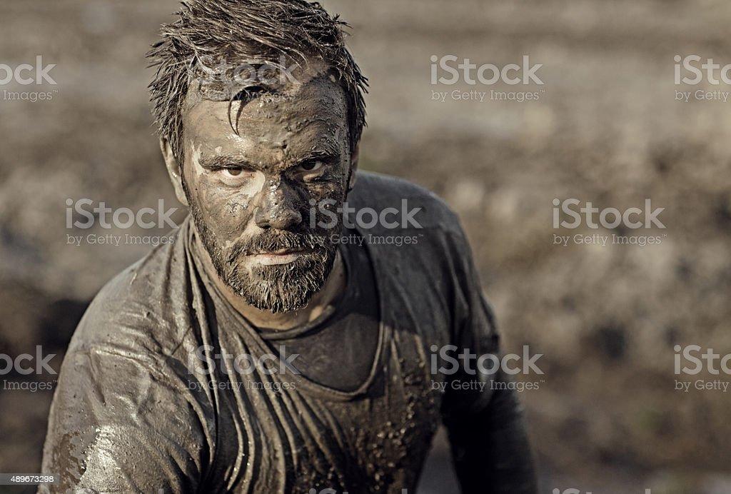 Dark haired man posing during a mud run stock photo