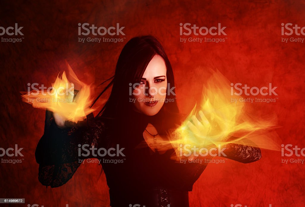 Dark haired sorceress throwing fire, horizontal on red. stock photo