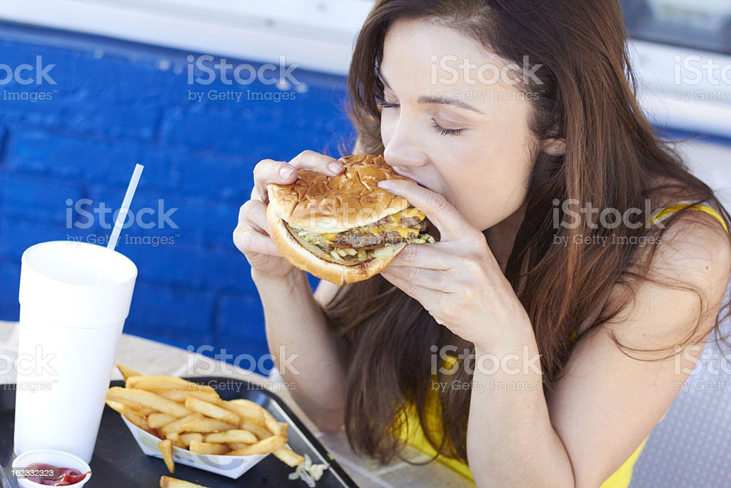 Dark haired woman eating a fast food burger and fries stock photo