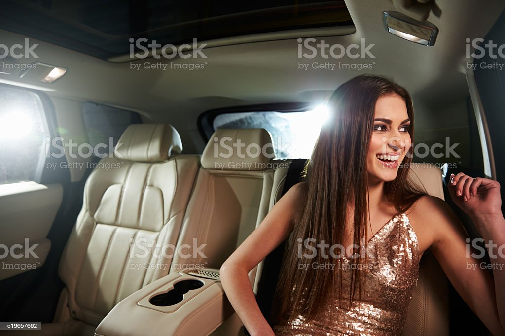 Dark haired young woman sitting in limo looks out stock photo