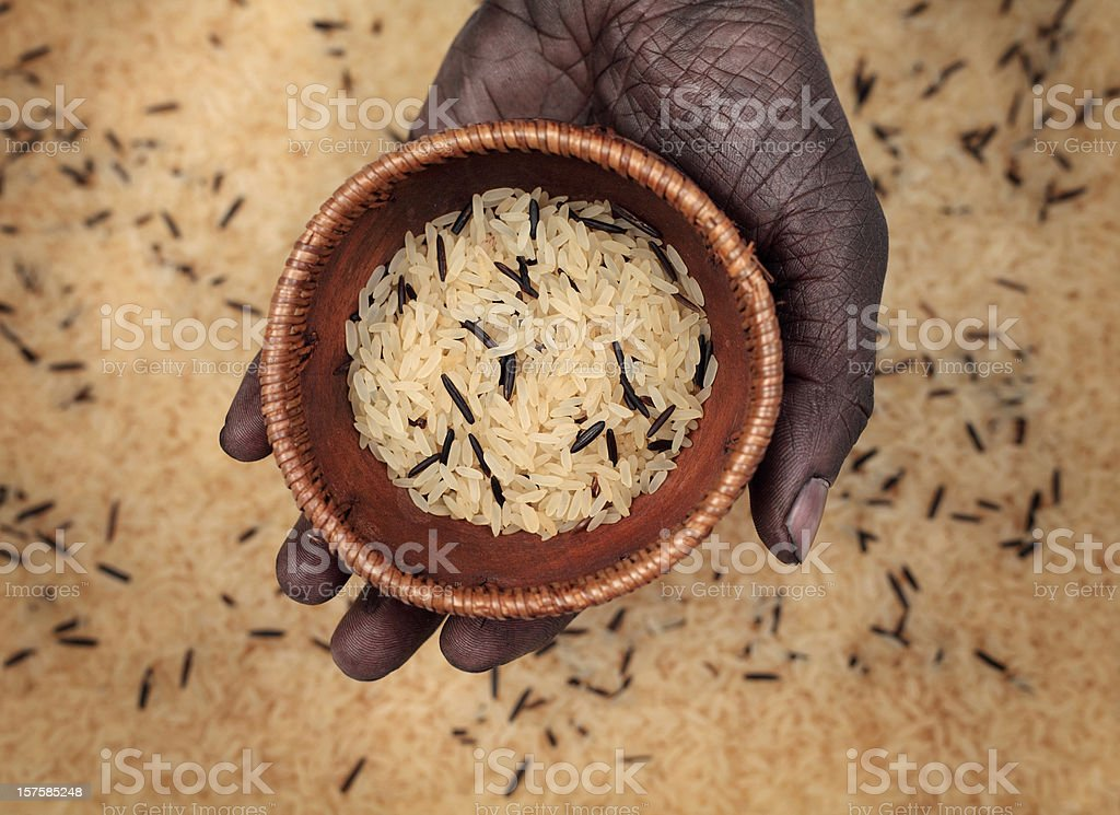 Dark Hand Holding Rice in Wooden Bowl royalty-free stock photo