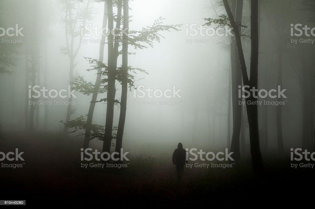 Dark horror man in creepy foggy forest stock photo