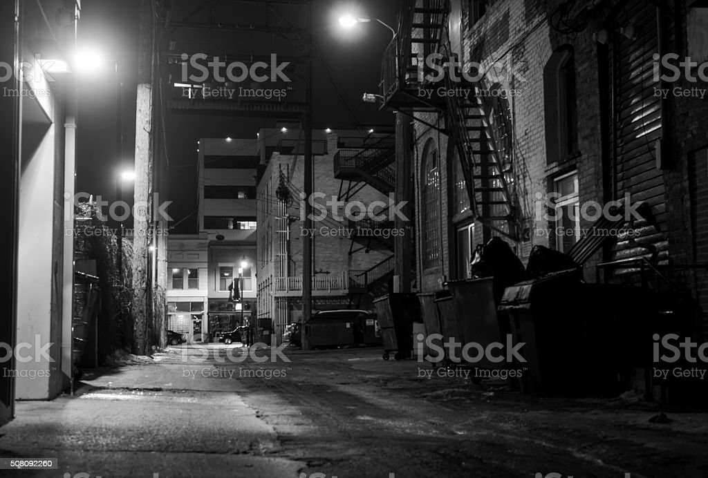 dark icy alleyway at night in black and white stock photo