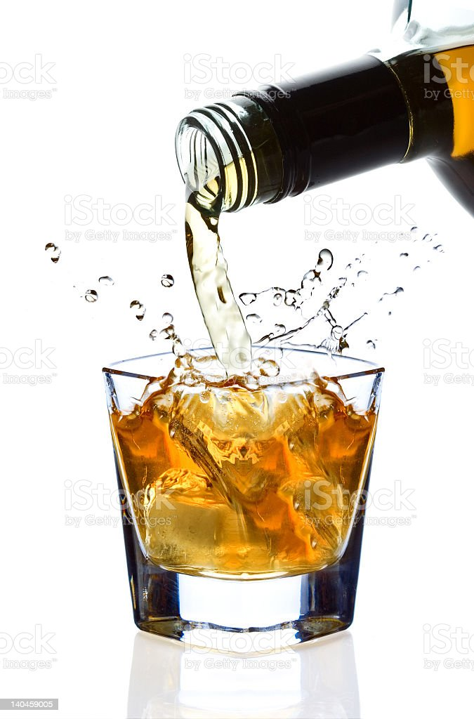 A dark liquor being poured into a glass of ice royalty-free stock photo