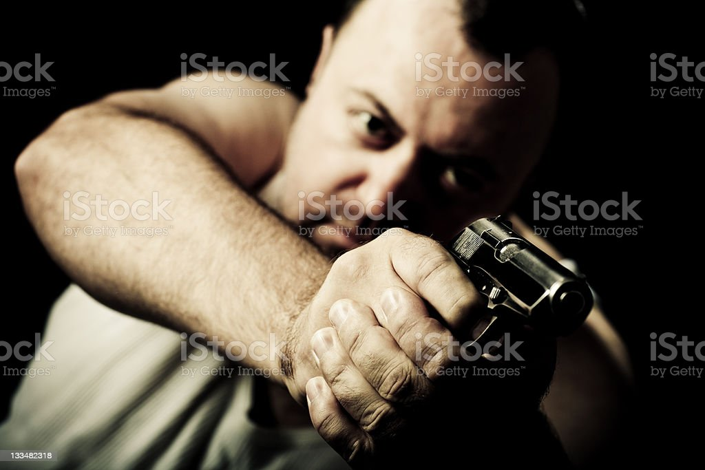 Dark man aiming with a gun royalty-free stock photo