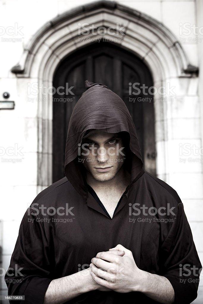 Dark Monk with Intense Gaze in Doorway Vertical stock photo