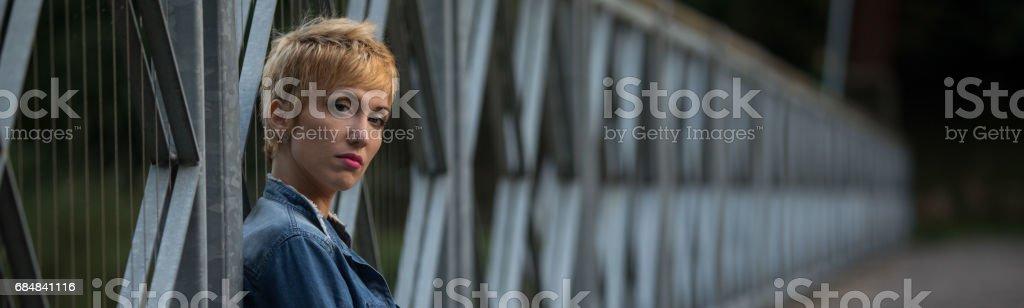 Dark moody panorama of a serious blond woman stock photo