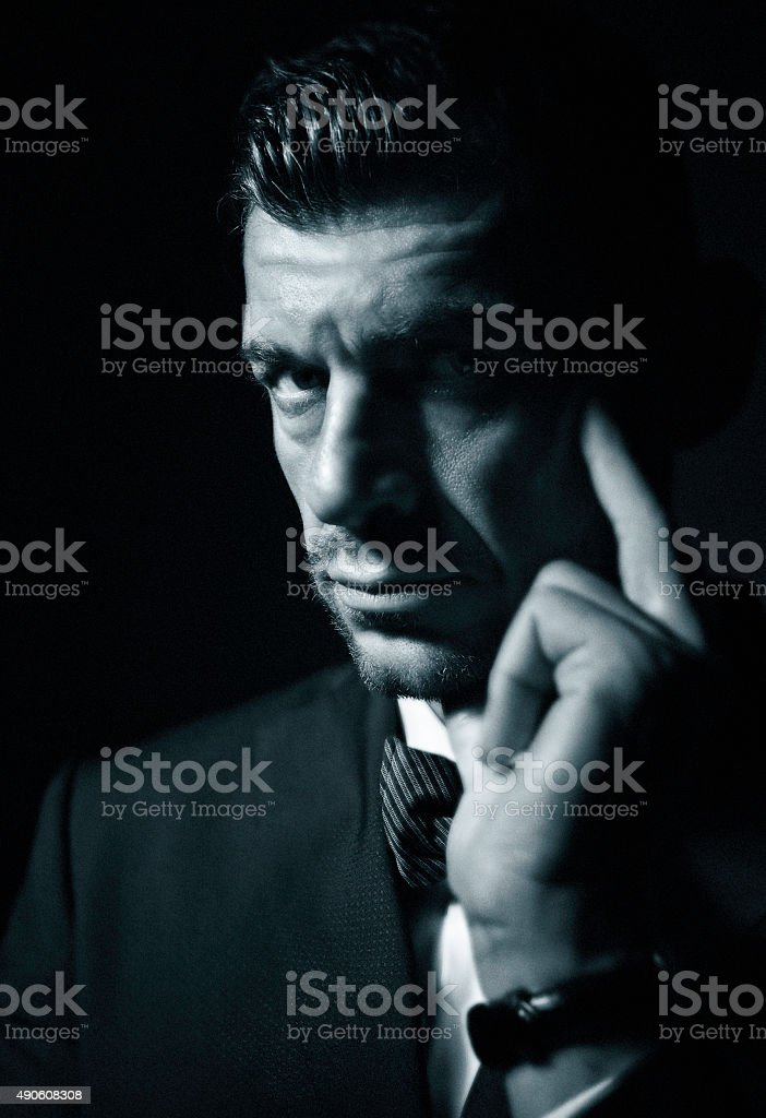 Dark, mysterious, pensive man in moody light stock photo