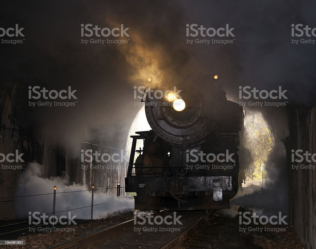 A dark picture of a steam locomotive entering a tunnel stock photo