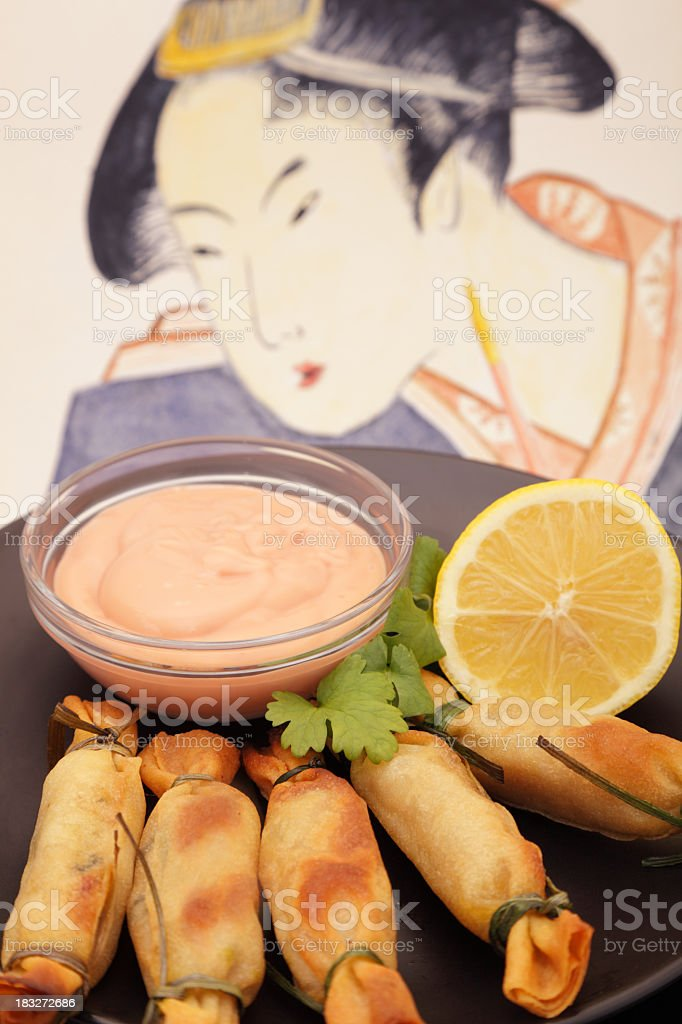 dark plate of asian prawn parcels with lemon and sauce stock photo