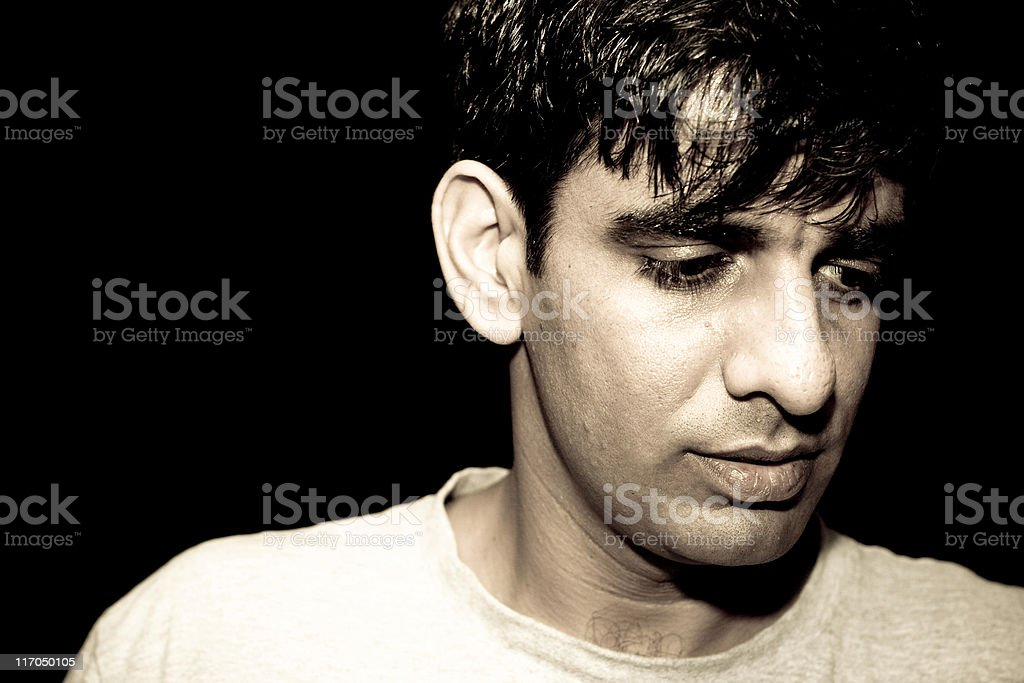 Dark portrait of One Pensive Indian young adult male royalty-free stock photo