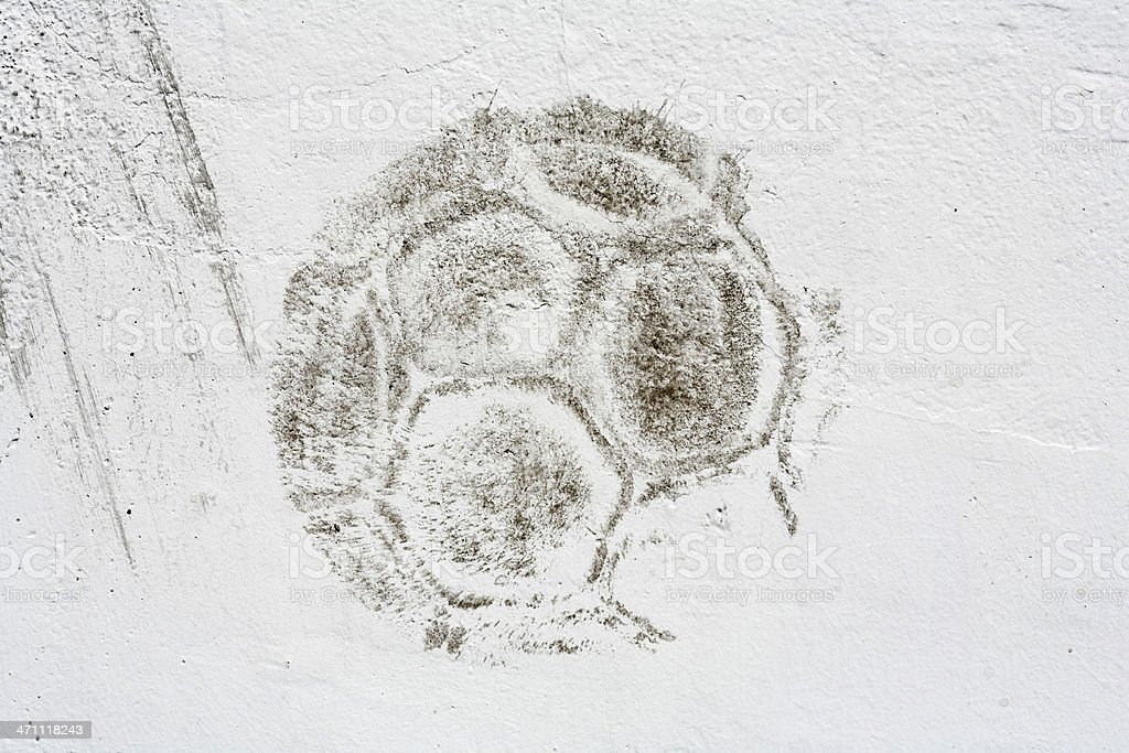 Dark print of soccer ball on white wall royalty-free stock photo