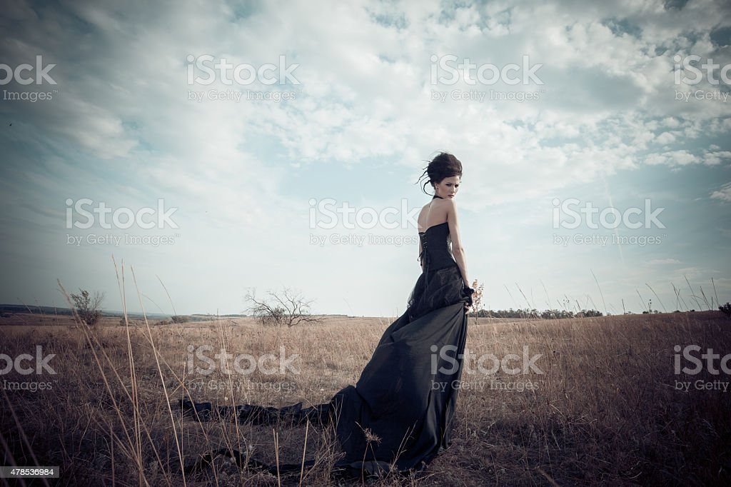 Dark Queen in field. Fantasy black dress. stock photo