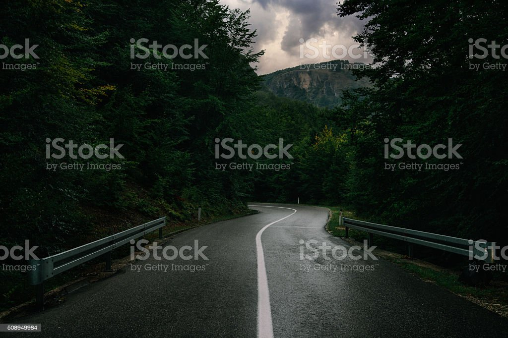 Dark rainy road through the forest of Durmitor national park stock photo