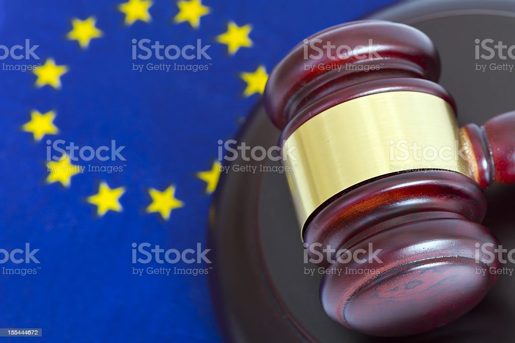 Dark red gavel with gold stripe and EU flag on background  stock photo