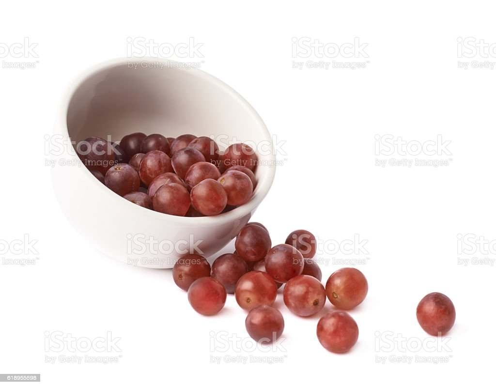 Dark red grapes spilled out of bowl stock photo