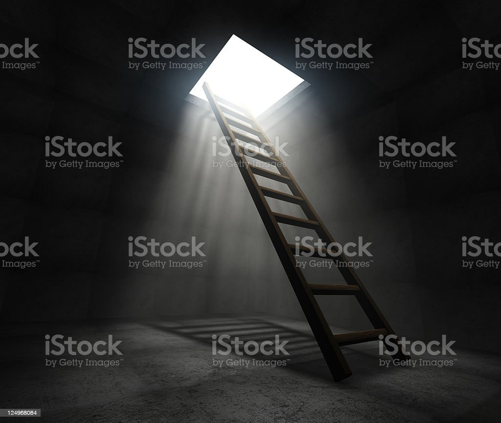 Dark room with a ladder to a lit up hole in the ceiling stock photo