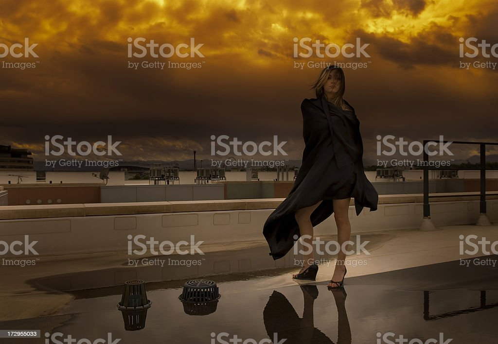 Dark Scene of a Mysterious Woman Wrapped in Black Cloak royalty-free stock photo