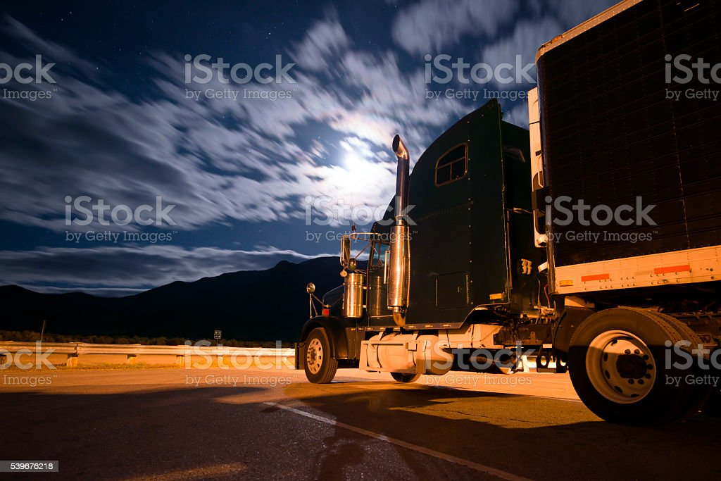 Dark semi truck reefer in night light with moony clouds stock photo