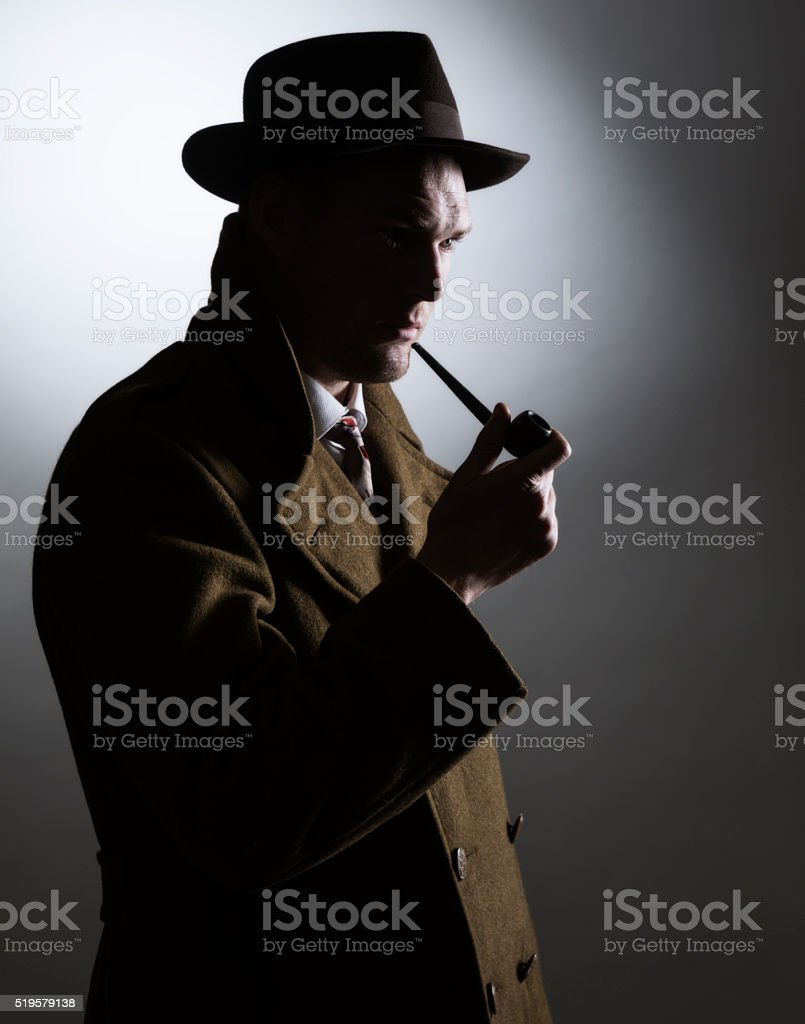 Dark Silhouette 1940s Gumshoe Private Eye Detective Holding Smoking Pipe stock photo