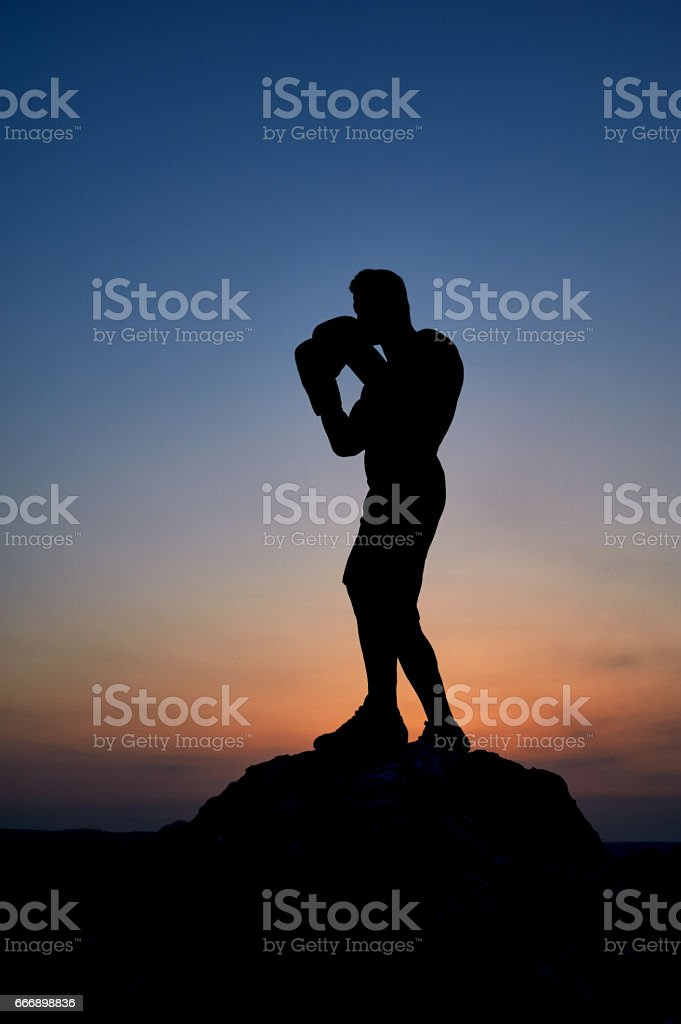 Dark silhouette of a muscular male boxer outdoors on sunset stock photo