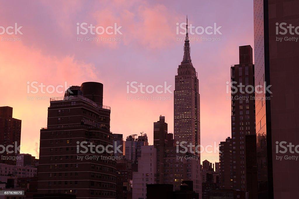 Dark silhouette tops of Manhattan cityscape, bright pink-orange sky stock photo