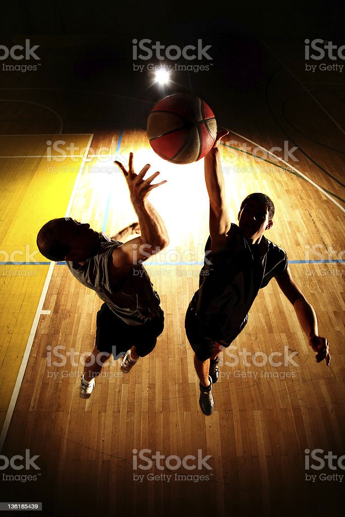 Dark silhouettes of jumping two basketball players stock photo