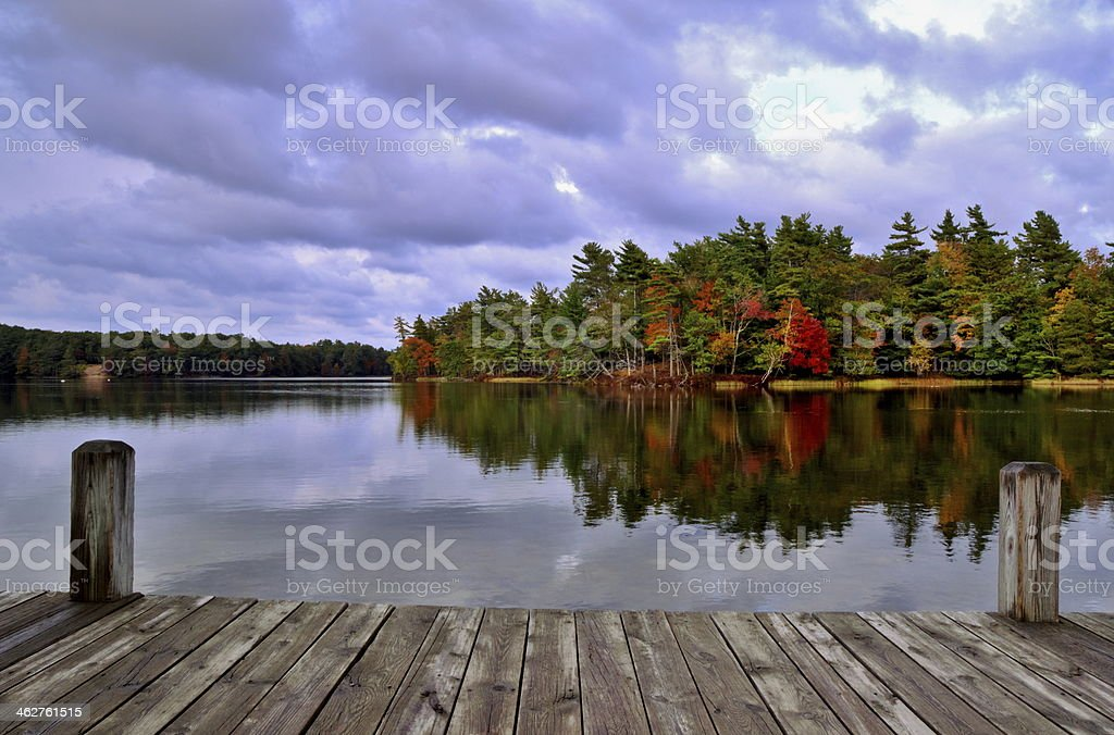 Dark skies over an autumn forest and lake from a wood dock  stock photo