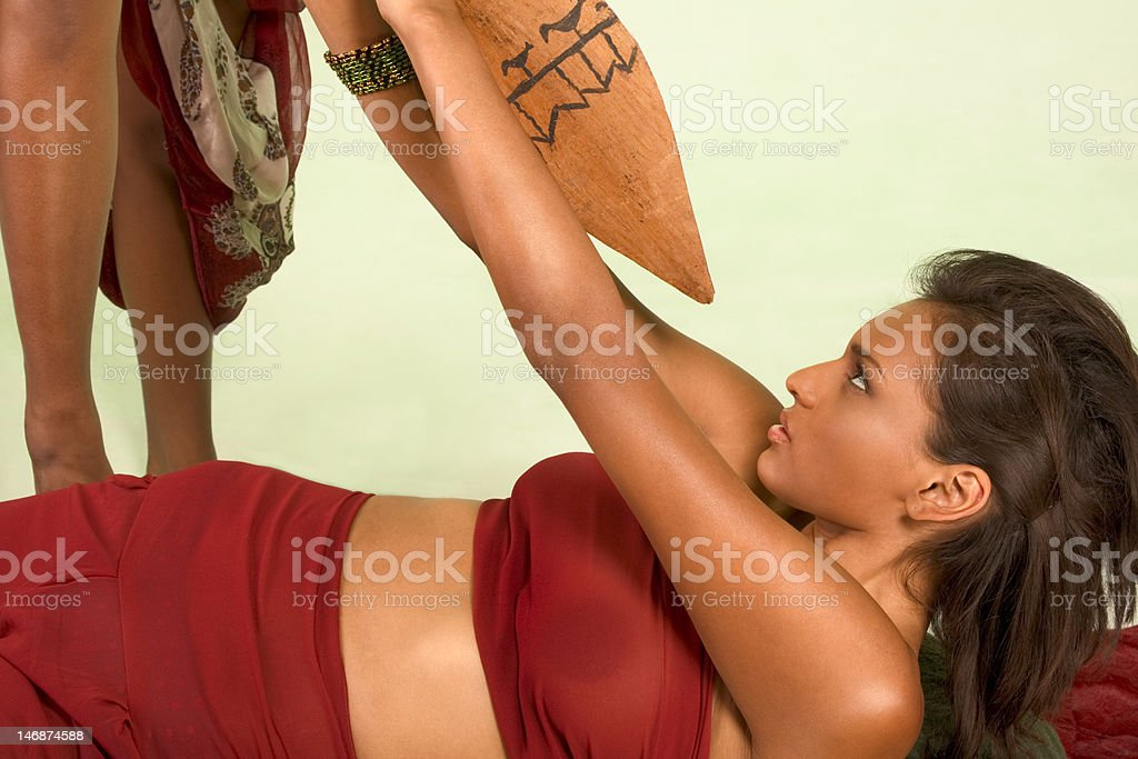 Dark skinned woman is attacked with use of spear royalty-free stock photo