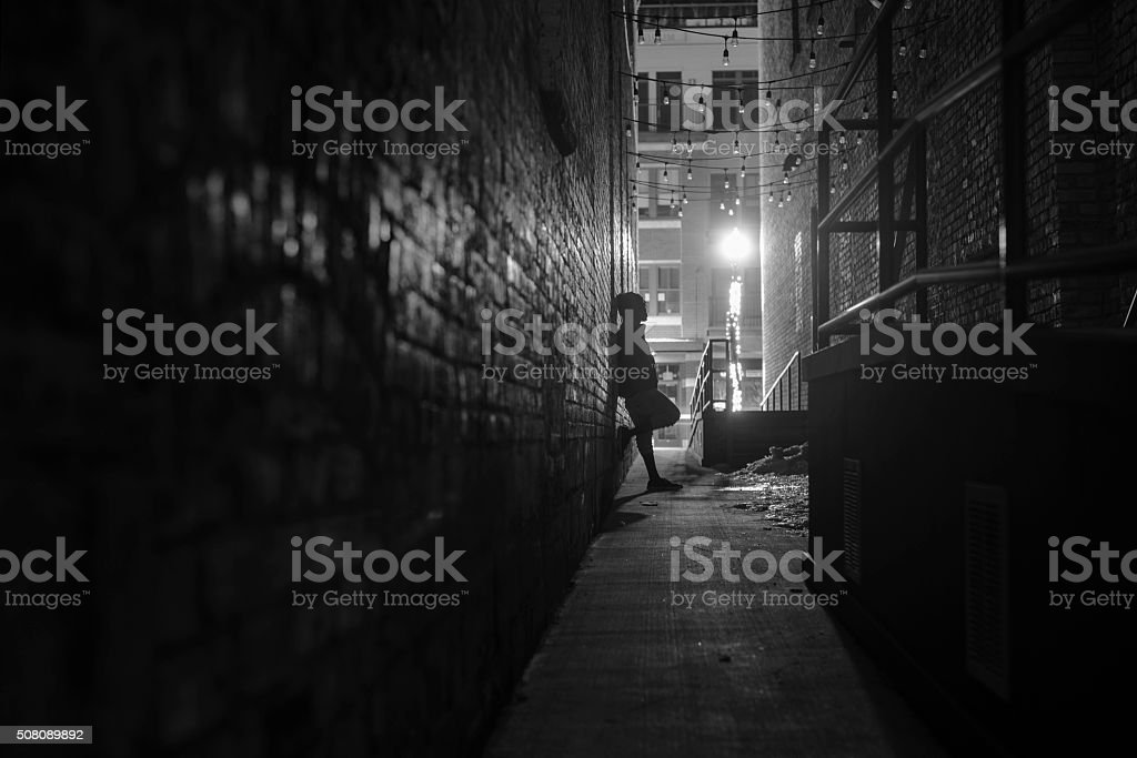 dark small alleyway at night with person by wall stock photo