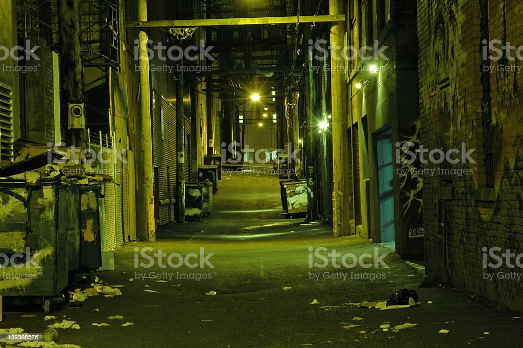 A dark, small alleyway pictured late at night stock photo