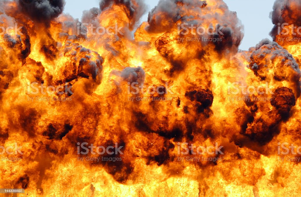 Dark smoke and flames rising from an explosion stock photo