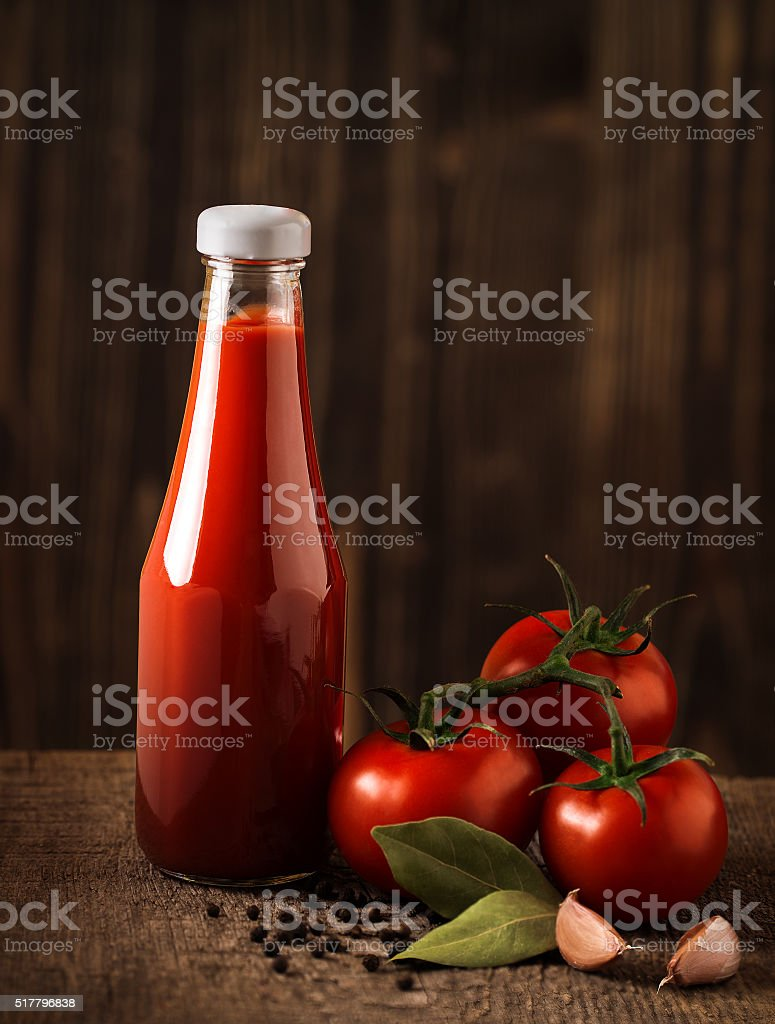Dark still life with ketchup and ingredients on the rough stock photo